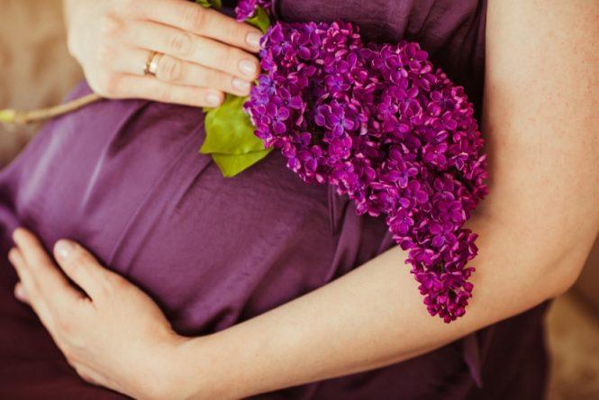 Gravid mave med lilla blomster - under graviditet